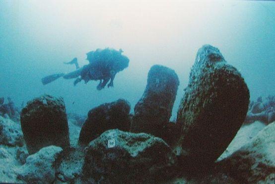 Дайвер проплывает мимо каменных монолитов