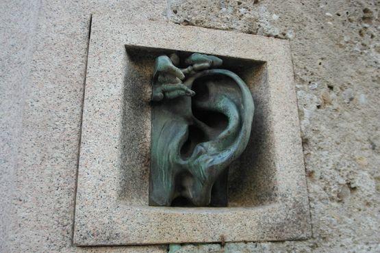 Бронзовое ухо на фасаде дома