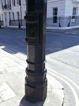 Основание фонарного столба; маленькая дверца видна в верхней части фото