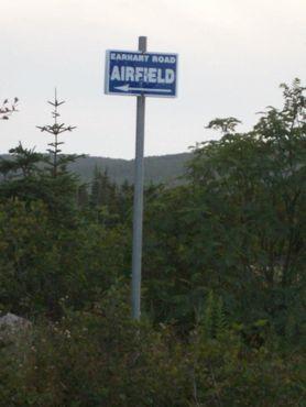 Этот знак указывает на дорогу к аэродрому. Длина Эрхарт-роуд составляет около 300 метров, и до неё можно добраться по Леди-Лейк-Роуд. Этот знак трудно заметить среди деревьев