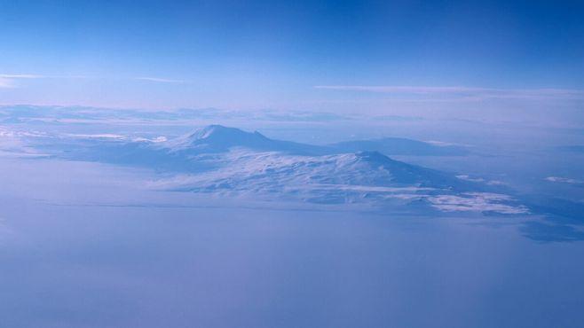 Слегка дымящаяся гора Эребус (слева) и гора Ужаса; вид с высоты 12.5 км на судне Pan Am Flight 50, 30 октября 1977 года © Brian Baum