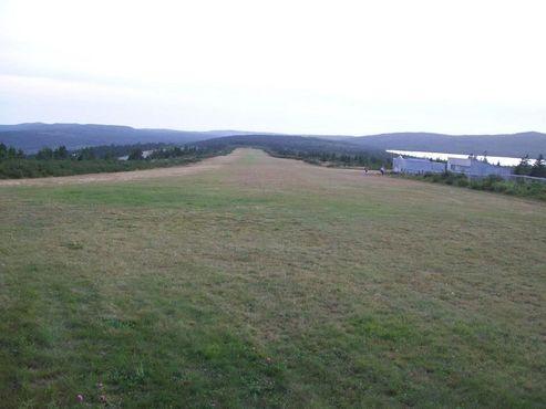 Вид на взлётно-посадочную дорожку от конца к началу. Как правило, посадки идут в этом направлении, взлёты совершаются в сторону холма, который позади фотографирующего