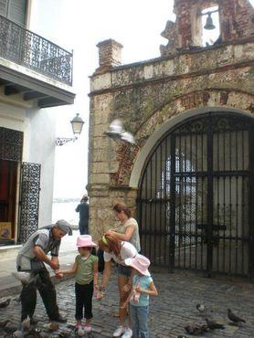Дети кормят голубей около часовни Святого Христа