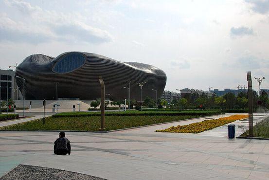 Одинокий мужчина сидит возле музея в Канбаши
