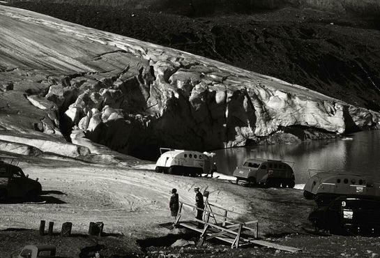 Это фотография приблизительно 1960 года, на ней запечатлены ранние снегоходы Бомбардье, перевозившие в то время людей на ледник. Фотография сделана в августе