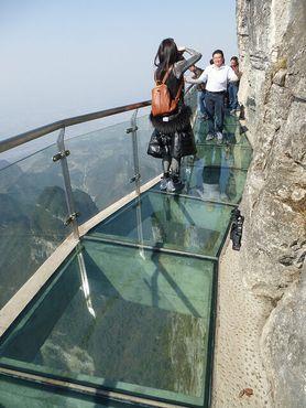 Туристы, идущие по стеклянному проходу