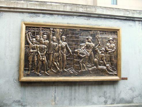 Мемориальная доска за пределами тюрьмы иллюстрирует пытки, которые практиковало французское колониальное правительство
