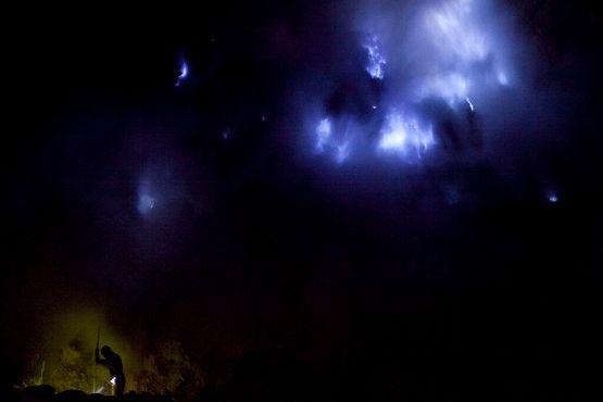 Горняк трудится под сияющим синим пламенем, вспыхивающим в Кавах Иджен