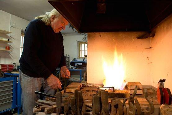 Вольфганг в своей кузнице подготавливает для реставрации детали исторических часов