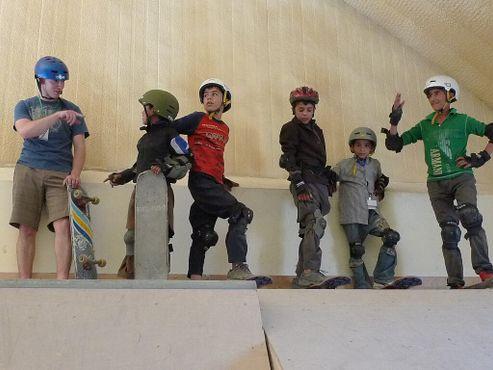 Капрал морской пехоты США Бретт Лазарофф учит мальчиков кататься на скейте